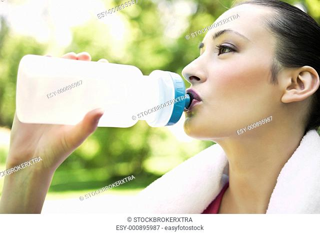 A beautiful caucasian woman doing exercise drinking water in a park
