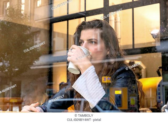 Young woman enjoying hot drink in cafe