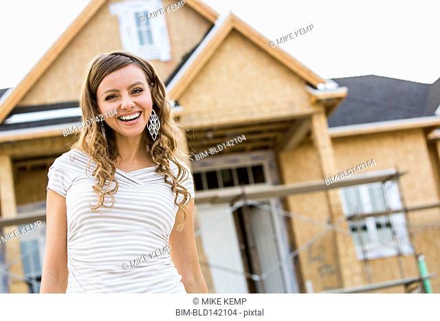 Caucasian woman smiling near house under construction