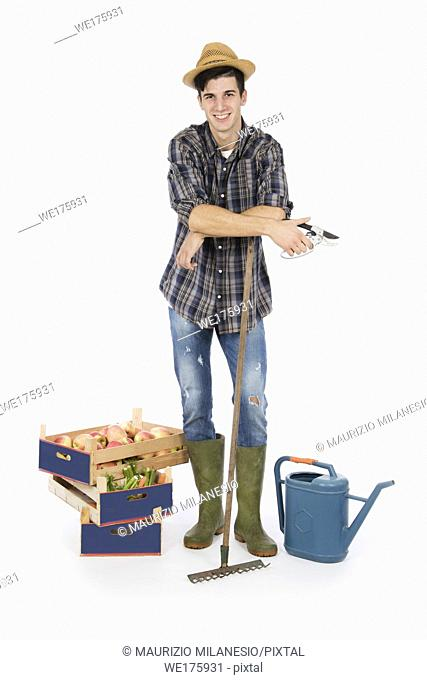 Young farmer with shears in hand and rake, at his feet crates with fruit and vegetables, he is wearing a straw hat, checked shirt and green rubber boots