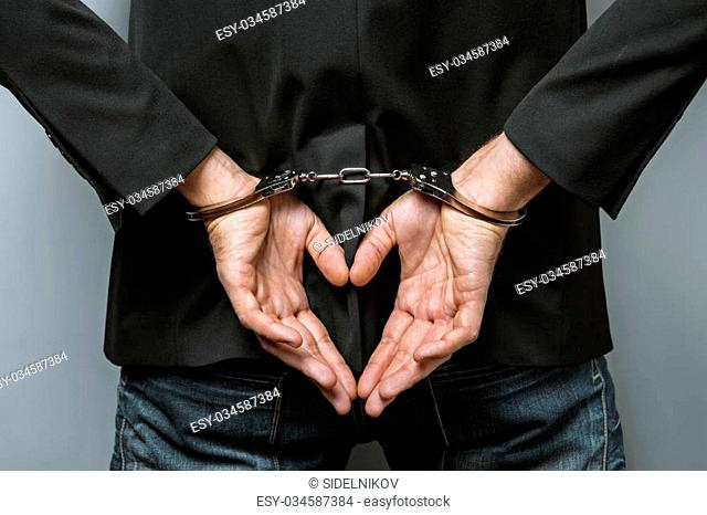 Studio shot of young businessman on grey background. Man wearing jacket. His hands with handcuffs. Back view