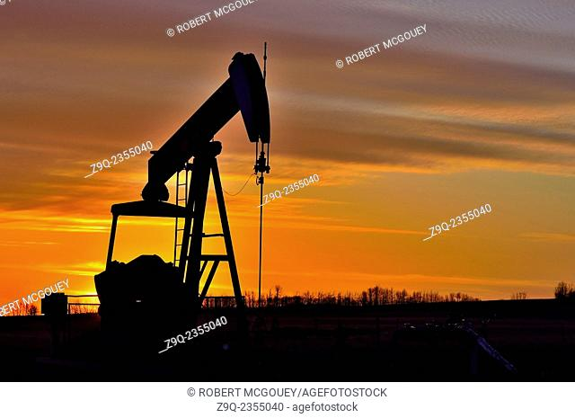 A horizontal image of a Pump Jack working at pumping crude oil from a wellhead silhouetted by the setting sun in rural Alberta Canada