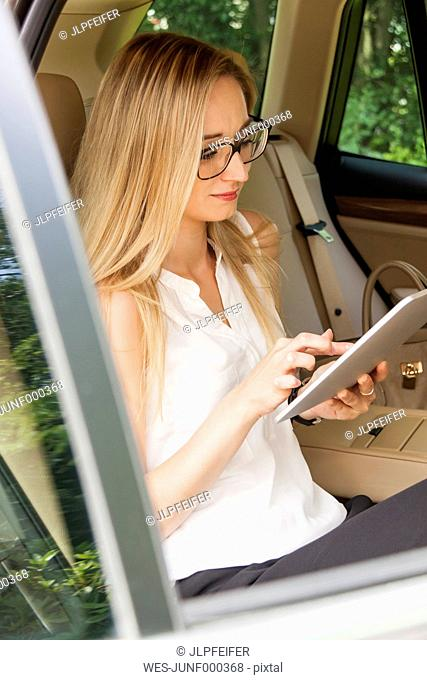 Blond woman sitting on back seat of a car using digital tablet