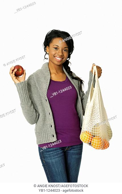Young woman with enviromentally-friendly reusable string shopping bag filled with fresh fruit, holding an apple