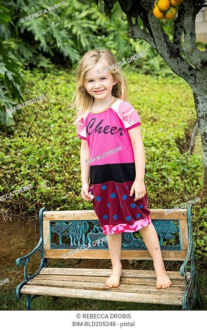Smiling girl standing on park bench