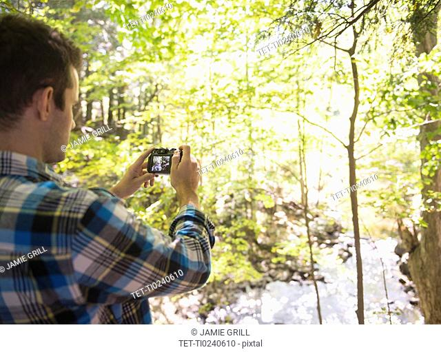 Man taking picture in forest