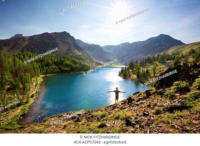 A hiker taking in the sunshine at Ladyslipper Lake, Cathedral Provincial Park, British Columbia, Canada