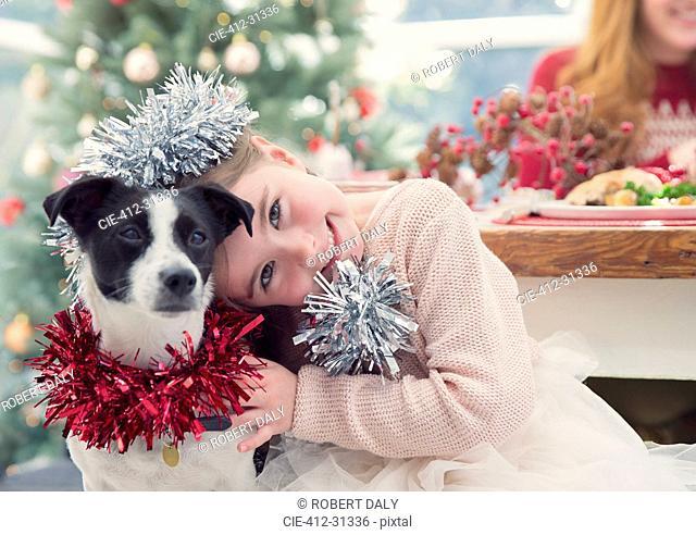 Portrait smiling girl hugging dog with Christmas decoration