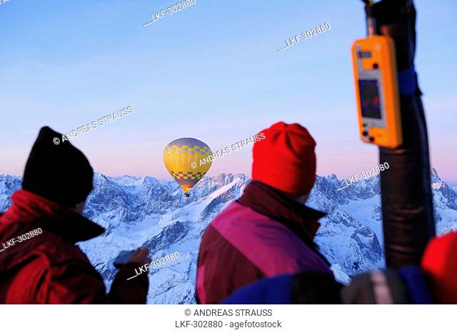 Two people on hot-air ballon ride looking towards hot-air balloon, snow covered mountains in background, Garmisch-Partenkirchen, Wetterstein range