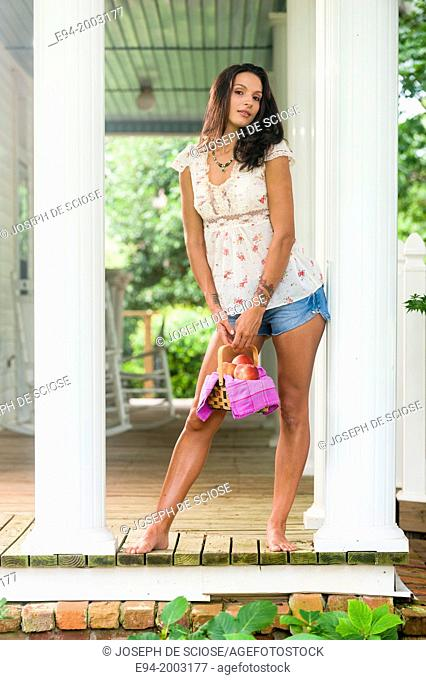 A 27 year old brunette woman wearing cut off shorts standing on a porch holding a basket of peaches