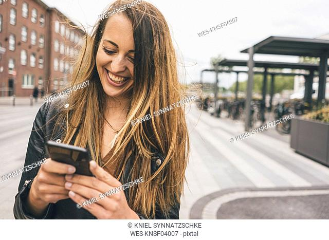 Happy young woman using cell phone in the city