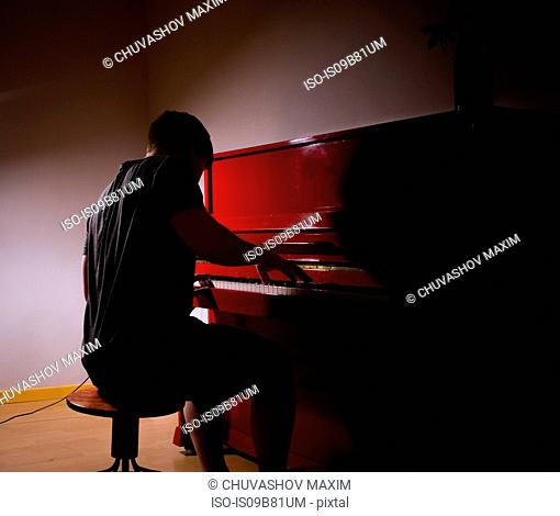Man playing piano in dimly lit room