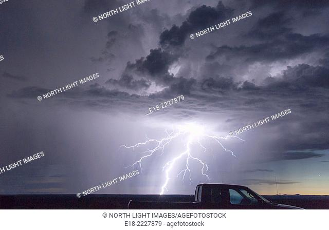 USA, New Mexico, Carson. Electrical storm behind pickup truck, over the Carson National Forest