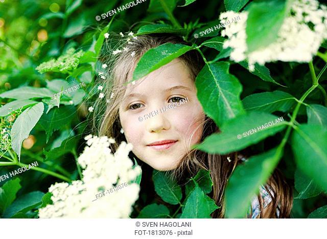 Portrait serene girl standing in flowering bush