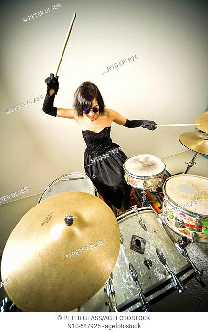 Woman, wearing an evening gown and blue sunglasses, playing the drums