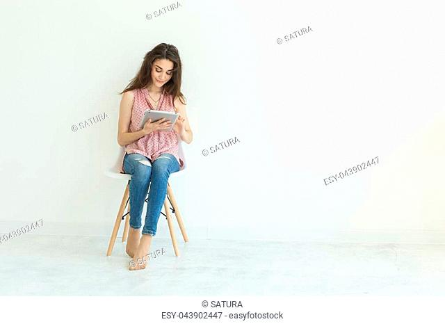 Technologies, education, people concept - young student woman using tablet on white background with copy space