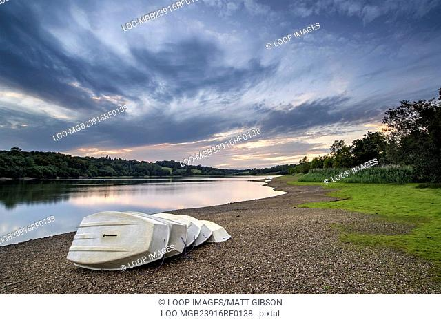 Summer sunset over lake in landscape with leisure boats on shore