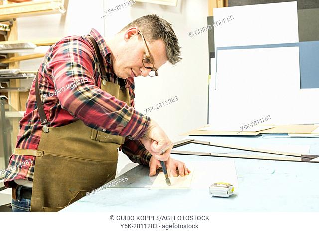 Goirle, Netherlands. Mid adult male craftsman and picture framemaker, cutting up sheets of glass for a new picture frame