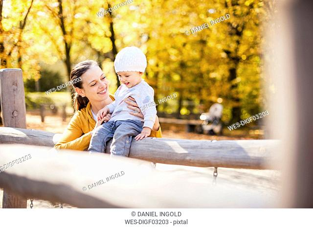 Happy baby girl and her mother having fun on a playground in autumn