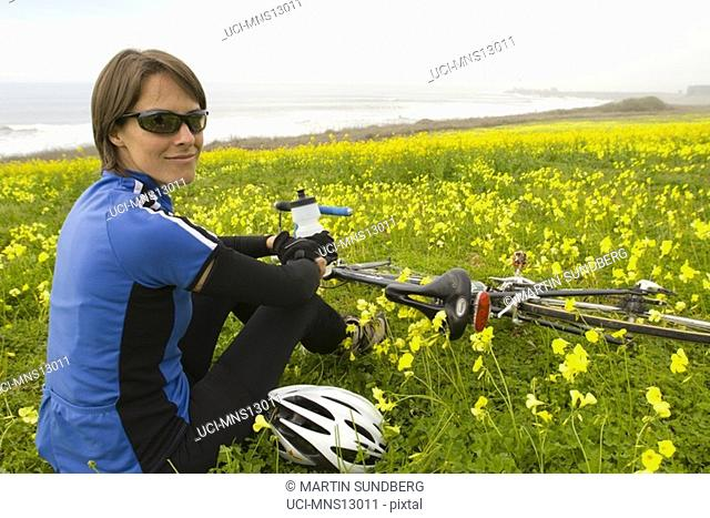 Female cyclist resting in flowery meadow, California