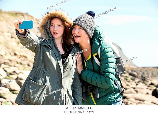 Mother and daughter taking selfie by seaside, Folkestone, UK