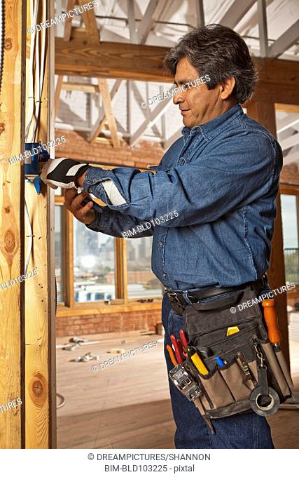 Hispanic electrician working on construction site