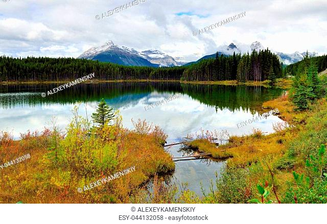 Beautiful high mountains of the Canadian Rockies reflecting in an alpine lake along the Icefields Parkway between Banff and Jasper during foliage season with...
