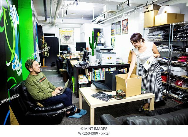 Design Studio. Two colleagues, man and woman, stocktaking and packing goods for sale and distribution. Teeshirts and hats