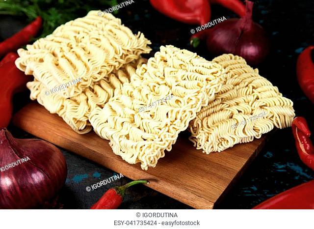 Raw instant asian noodles on wooden board