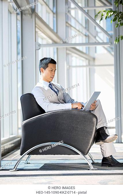 Businessman using digital tablet in lobby