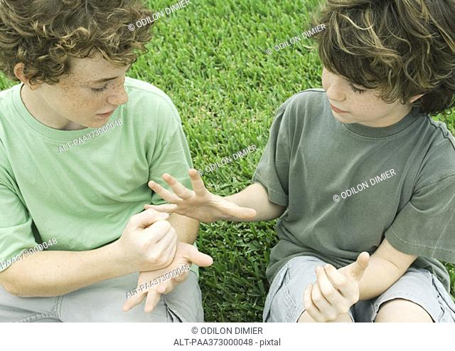 Two boys playing rock paper scissors
