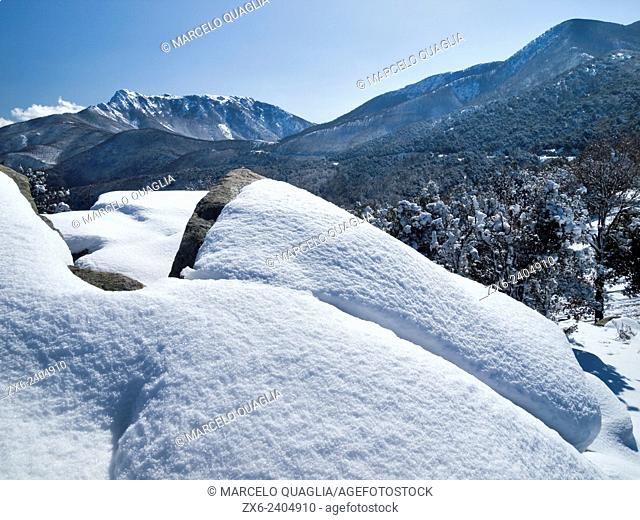 General view of Montseny Natural Park on a sunny morning after a heavy snow storm, with Agudes peak at the far left. Barcelona province, Catalonia, Spain