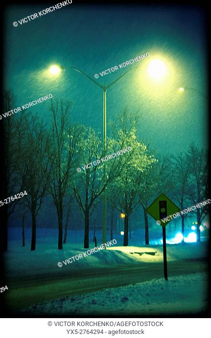 Snow falling on a deserted street at night in Toronto suburbs