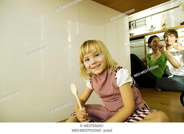 Girl 4-5 in kitchen, portrait, parents in background