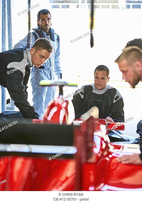 Formula one driver watching pit crew repairing race car in repair garage