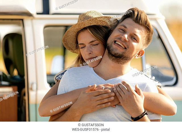 Happy affectionate young couple at camper van