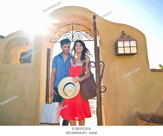 Young couple arriving at sunlit villa on vacation, smiling