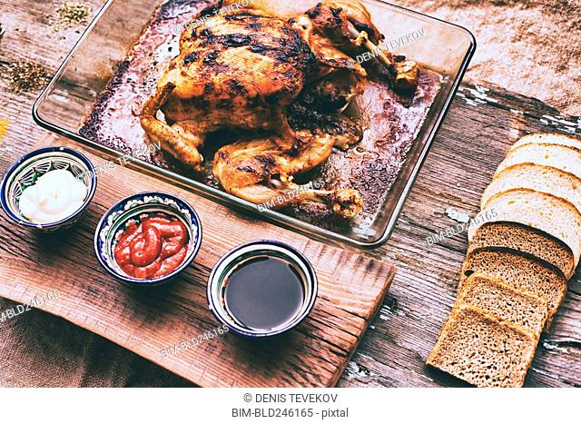 Close up of roasted chicken with bread and sauces on wooden table