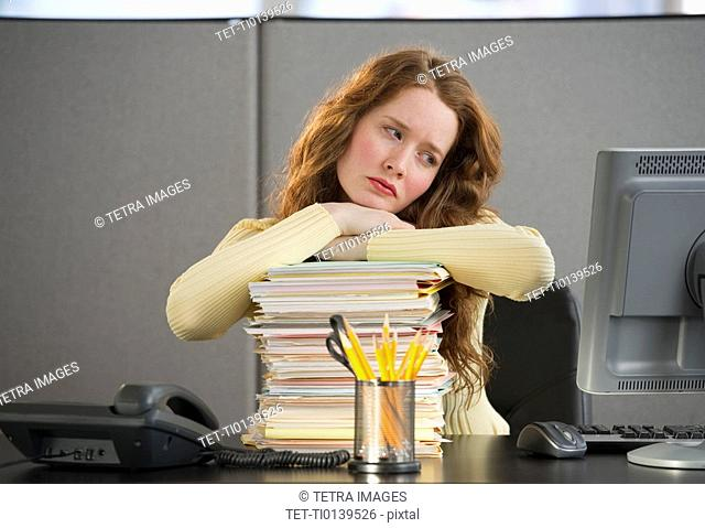 Overworked woman in cubicle