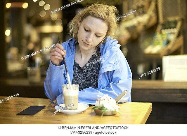 Young thoughtful woman stirring latte macchiato with drinking straw, in cafe, taking a break alone, thinking, in Munich, Germany