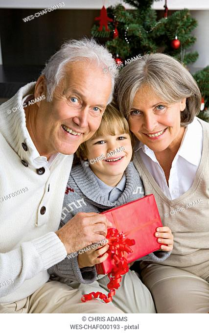 Happy little boy receiving Christmas present from his grandparents