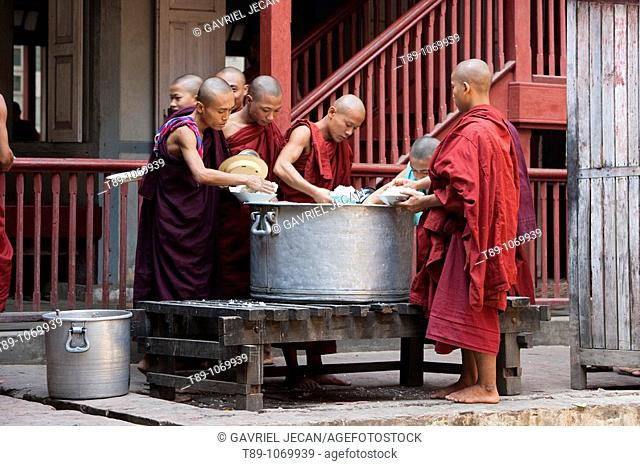 Monks waiting in line and holding alms woks