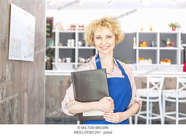 Smiling waitress in restaurant holding menu
