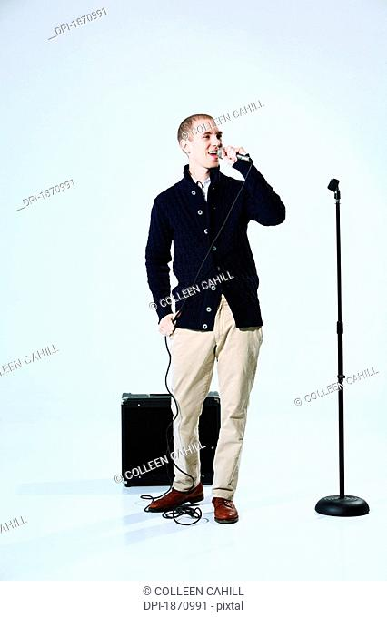 a young man singing into a microphone