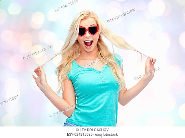 emotions, expressions, summer and people concept - smiling young woman or teenage girl in heart shape sunglasses holding her strand of hair over holidays lights...