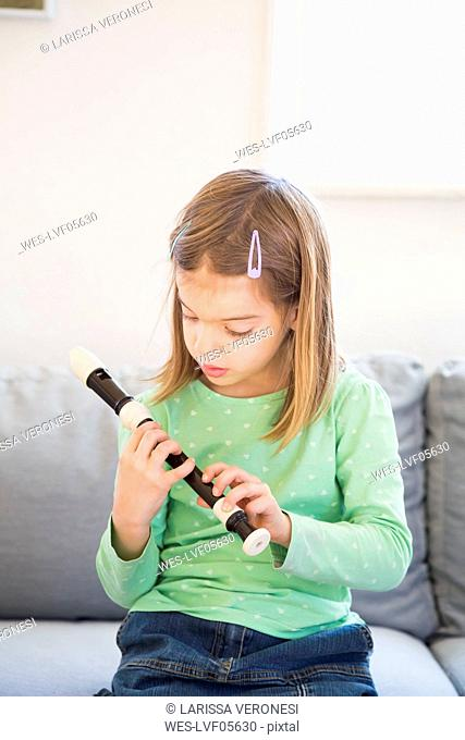 Little girl sitting on couch with recorder