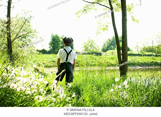 Italy, back view of little boy wearing vintage clothing enjoying nature