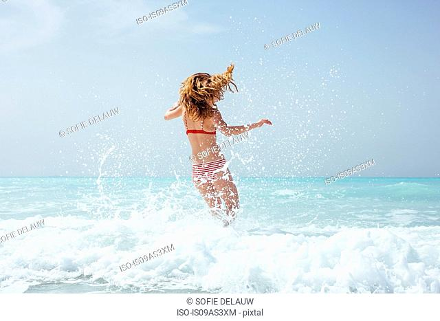 Rear view of young woman wearing bikini running in sea