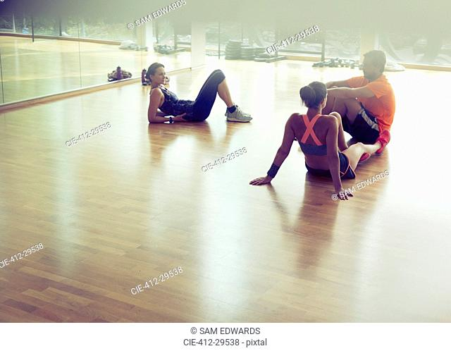 Friends resting and talking on gym studio floor
