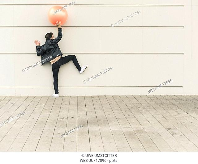 Young man in leather jacket, playing with a gym ball